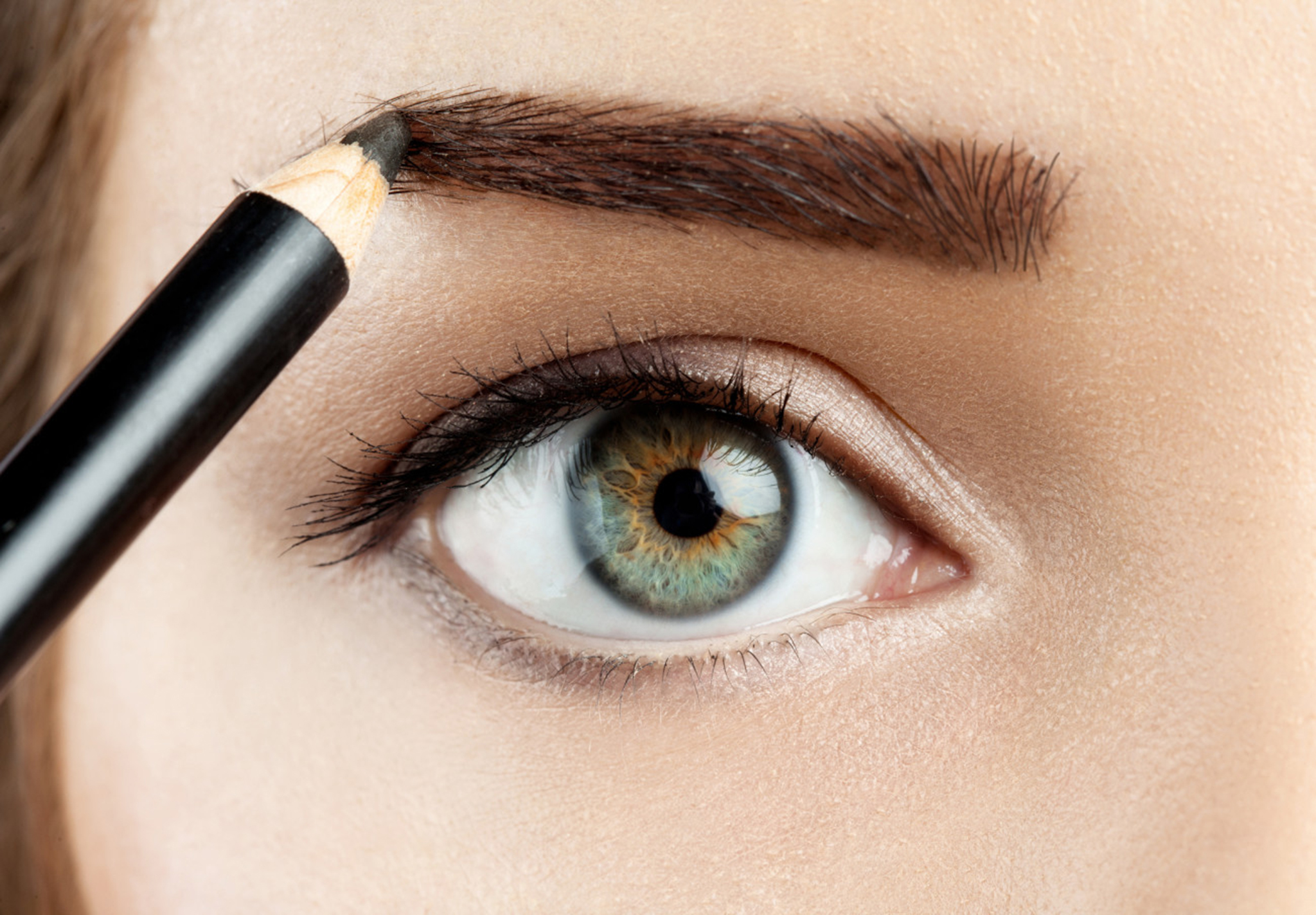 young woman draws a shape eyebrows eyebrow pencil brown